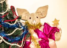 Symbol of 2019, a toy pig next to an elegant Christmas tree on a light background.  stock images