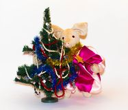 Symbol of 2019, a toy pig next to an elegant Christmas tree on a light background.  stock photo