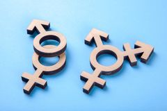 Symbol of transgender and gender symbols of man and woman of tree on blue. Background royalty free stock photo