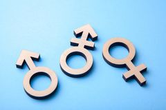Symbol of transgender and gender symbols of man and woman of tree on blue. Background stock photo
