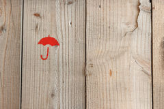 Symbol umbrella in red on wood texture, Stock Image