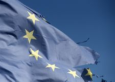 Symbol of unity. Torn EU flag wave on blue sky. European Union flag with twelve stars on sunny outdoor. Euro skepticism. Concept royalty free stock images