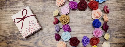 Symbol of Valentine`s day. Gift box with group of roses over wooden table. Top view. royalty free stock photography