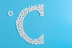 Symbol von Celsius wird mit einer weißen Pille auf blauem Hintergrund ausgebreitet lizenzfreie stockbilder
