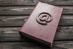 Symbol von E-Mail auf einem Buch auf einem hölzernen Hintergrund lizenzfreie stockfotos