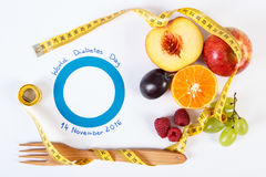 Symbol of world diabetes day and fresh fruits with centimeter. Fresh fruits with tape measure and blue circle of paper, concept of slimming and symbol of world Royalty Free Stock Photo