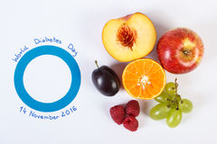 Symbol of world diabetes day and fresh fruits on white background. Fresh ripe fruits and blue circle of paper, symbol of world diabetes day and healthy nutrition Royalty Free Stock Photo