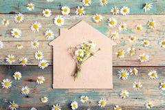 Symbole à la maison avec des camomilles sur le fond en bois de vieille turquoise Photographie stock libre de droits