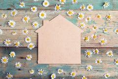 Symbole à la maison avec des camomilles sur le fond en bois de vieille turquoise C Photographie stock libre de droits