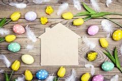 Symbole à la maison avec des oeufs de pâques, des poulets et des tulipes jaunes sur vieux Photos stock