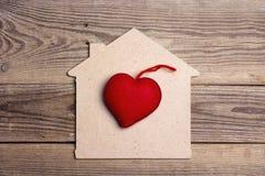 Symbole à la maison avec le coeur rouge sur le fond en bois Image stock