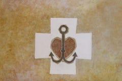 Symbole chrétien : ancre, coeur, croix sur un fond jaune Dalle de marbre avec l'ornement ou la mosaïque La décoration de religieu photographie stock