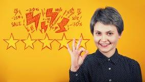 Symbole correct de femme d'apparence heureuse de hippie comme approbation et comme le geste, supports au-dessus de mur jaune Exci image stock