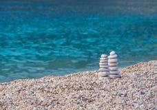 Symbole d'équilibre des pierres sur une plage grecque photographie stock