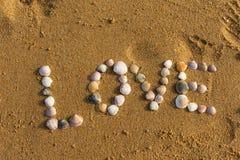 Symbole d'amour écrit sur le sable avec des interpréteurs de commandes interactifs Photos libres de droits