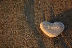 Symbole d'amour Coeur de pierre sur le Pebble Beach Fond de Valentine Photographie stock libre de droits