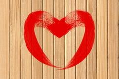 Symbole d'amour de coeur de dessin sur le mur en bois jaune Image stock