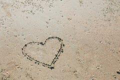 Symbole d'amour de coeur dessiné par doigt sur la plage de mer Image stock