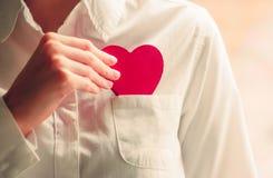 Symbole d'amour de forme de coeur chez des mains de la femme Images stock
