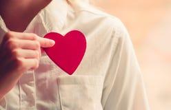 Symbole d'amour de forme de coeur chez des mains de la femme Photographie stock libre de droits
