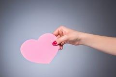 Symbole d'amour de forme de coeur chez la main de la femme Image libre de droits
