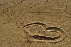 Symbole d'amour dessiné dans le sable Photographie stock libre de droits