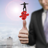 Symbole de équilibrage de pour cent d'homme d'affaires sur un autre pouce de grande main Photo stock