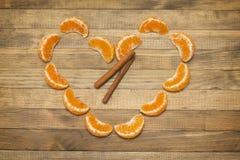 Symbole de cannelle et de coeur de bâton deux fait de mandarine Photographie stock