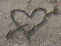 symbole de coeur avec la flèche dessinée sur la plage Photographie stock libre de droits