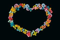 Symbole de coeur créé par les lettres colorées en plastique sur le tableau noir Image libre de droits