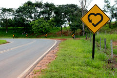 Symbole de coeur d'amour au signe de route jaune Images stock