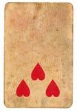Symbole de coeur de trois rouges sur le vieux fond de papier jouant de carte Photographie stock