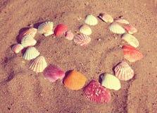 Symbole de coeur des coquilles sur le sable - rétro style de vintage Photographie stock libre de droits