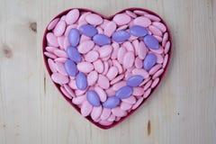 Symbole de coeur des dragées de chocolat sur le fond en bois, concept d'amour Photos stock