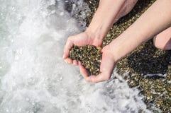 Symbole de coeur des pierres dans une main femelle sur un fond noir de la mer Photo stock