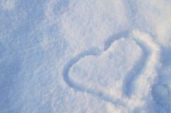 Symbole de coeur dessiné sur la neige de scintillement blanche pure Images stock