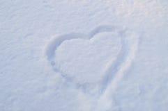 Symbole de coeur dessiné sur la neige de scintillement blanche pure Photos stock