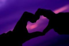 Symbole de coeur pourpre fait avec des mains Image stock