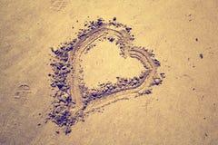 Symbole de coeur tiré par la main sur la plage sablonneuse Photographie stock