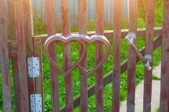 Symbole de coeurs sur la barrière de la porte de guichet dans le village Photos stock