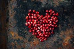 Symbole de jour de valentines - coeur rouge fait à partir des graines de grenade sur le fond noir Photos stock