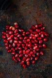 Symbole de jour de valentines - coeur rouge fait à partir des graines de grenade sur le fond noir Photos libres de droits