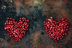 Symbole de jour de valentines - coeur rouge fait à partir des graines de grenade sur le fond noir Photographie stock libre de droits