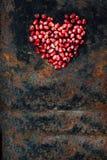 Symbole de jour de valentines - coeur rouge fait à partir des graines de grenade sur le fond noir Photo libre de droits
