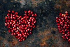 Symbole de jour de valentines - coeur rouge fait à partir des graines de grenade sur le fond noir Photographie stock