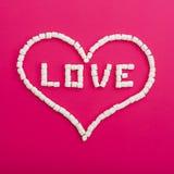 Symbole de l'amour fait de guimauves sur le fond rose Coeur Configuration plate Vue supérieure Photos stock