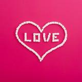 Symbole de l'amour fait de guimauves sur le fond rose Coeur Configuration plate Vue supérieure Photo stock