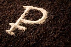 Symbole de logotype de rouble écrit sur la terre brune Photo libre de droits