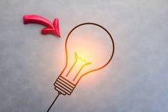 Symbole de lueur d'ampoule avec la flèche rouge sur le fond gris Photos libres de droits