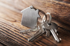 Symbole de maison avec la clé argentée sur le fond en bois Image libre de droits